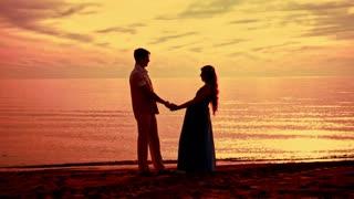 Couple beach sunset. Couple silhouette beach. Pregnant couple sunset. Love couple sunset. Silhouette couple kissing at golden sunset. Love couple kissing on sea beach at sunset. Couple sunset beach