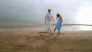 Couple draw heart symbol on sand. Romantic couple drawing heart shape on beach. Love couple on sea beach. Romantic vacation. Young couple draw heart sand. Couple beach