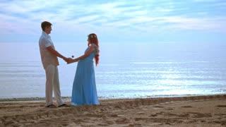 Couple holding hands on sea beach at sunrise. Pregnant couple beach. Happy couple beach. Beach holidays. Honeymoon vacation. Couple beach happy. Romantic couple beach. Love couple beach. Couple beach