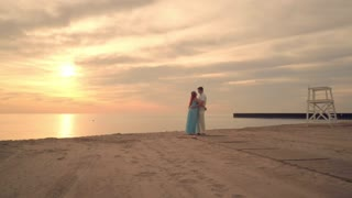 Couple kissing on sea beach at sunset. Love couple hugging on beach at evening. Golden sunset at sea beach. Pregnant couple on sand beach at sunset. Sunset sea beach. Relationship concept