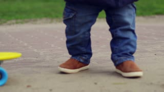 Cute child in jeans walking near skateboard. Baby feet in brown shoes. Kid legs in outdoor stand and walk. Little boy feet and skateboard in spring. Kid in blue clothes