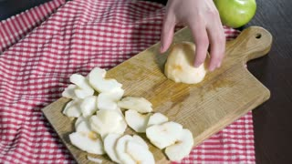 Cutting apple on slices. Preparing ingredients for baking apple pie. Chef slicing healthy apple at wooden plank in kitchen. Slicing peeled apples