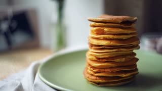 Dessert for morning breakfast. Man takes pancake from pancake stack. Sweet food for morning breakfast. Closeup of stack of delicious pancakes in green plate on table. American pancake breakfast