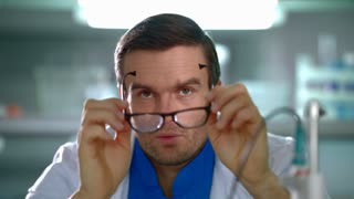 Doctor looking through glasses. Close up of researcher squints eyes holding glasses in hands. Laboratory worker having trouble with glasses. Doctor in lab hold eyeglasses