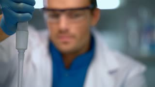 Doctor using micropipette in laboratory. Scientist working in lab. Clinician doing chemical research. Close up of chemist analyzing liquid sample. Lab man using modern laboratory equipment.