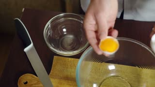 Egg falling in glass bowl. Baking ingredients, separating the yolk from the protein. Preparing ingredients for baking cake. Cooking food. Fresh organic eggs falling into bowl. Food ingredient