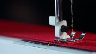 Electric sewing machine embroider on fabric. Sewing needle stitching in slow motion. Sewing machine needle work process. Sewing machine in slow motion. Manufacturing equipment