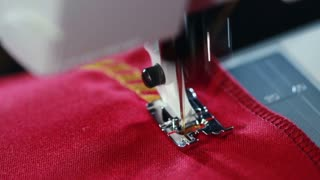 Embroidery machine. Sewing machine embroider pattern on the fabric. Sewing needle stitching seam on fabric in slow motion. Yellow thread pattern on red fabric. Sewing machine slow motion