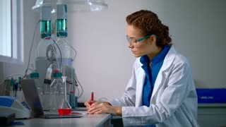 Female chemist in lab. Chemistry research. Chemist woman working with liquid in chemical laboratory. Woman chemist doing chemical research. Young chemist check chemical liquid in glass flask