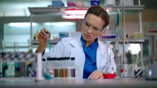 Female chemist in laboratory. Chemist analyzing chemical liquid in test tube. Woman chemist conducting chemical research in chemistry lab. Chemist woman working with chemical reagents in lab flask