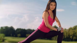 Female runner stretching legs outdoor at sunny day. Asian woman doing stretch exercise for legs. Fit girl warming up legs before fitness workout. Woman warm up legs in park