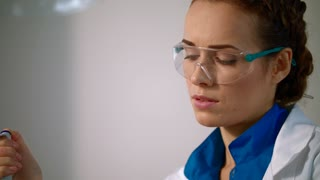 Female scientist face close up. Woman scientist in safety glasses. Science woman with safety glasses working in science laboratory. Portrait of scientist woman working in lab. Attractive scientist