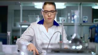 Female scientist preparing for experiment in pharmaceutical laboratory. Pharmacist preparing for pharmaceutical research in chemical lab. Assistant preparing for working in research laboratory.