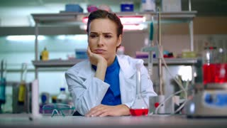 Female scientist waiting research results. Female scientist looking on laboratory equipment. Close up of tired woman scientist in lab. Portrait of scientist woman boring in lab