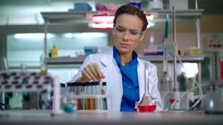 Female scientist working at the laboratory. Scientist cure. Woman scientist check test tube with reagents. Lab scientist observing liquid in laboratory. Worker doing science laboratory research