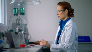 Female scientist working with scientist tablet in lab. Female researcher working in lab. Scientist woman using ipad in science laboratory. Scientist research on tablet pc. Modern research laboratory