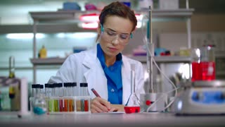 Female scientist working with scientist tablet. Woman scientist using tablet computer in modern laboratory. Scientist woman working in lab. Scientific research on tablet pc at research lab