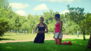 Fit girls talking kneeling on green grass in park. Two sport girls talk before fitness training outdoor. Multiracial girlfriends talks outdoor. Young girls stay on knees on green grass and talking