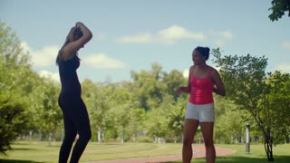 Fitness girls talking in park at summer day. Young female friends talking outdoor. Multiracial active lifestyle woman. Two fitness girls in sport clothes chatting together