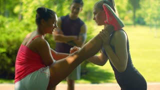 Fitness instructor helps female runner to do stretching exercise. Multi ethnic friends training in park. Trainer helping girl in leg stretching. Fitness woman doing stretching exercise outdoor