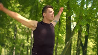 Fitness man exercising in park. Fitness exercise. Sport guy warming up shoulders outdoor. Handsome male runner stretching at park in slow motion. Outdoor workout. Cross fit. Male runner training