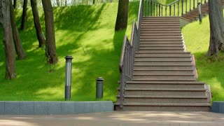 Fitness man run up stairs in slow motion. Young man running upstairs with dumbbells at park. Fit man in sport clothes run up stairs. Man fitness workout. Healthy lifestyle. Man climbing stairs