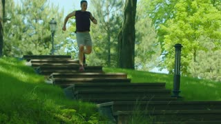 Fitness man running down stairs in slow motion. Running man on staircase. Runner training on stairway in park. Man fitness workout outdoor. Man jogging down stairs in park. Cardio exercise