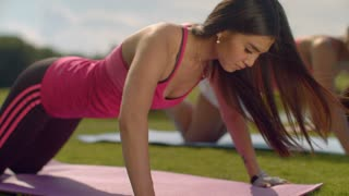 Fitness woman pushups. Strong woman doing push up exercise. Closeup of asian woman training outdoor. Sporty woman push ups exercise. Fit girl pushing in park at sunny day. Asian girl outdoor fitness