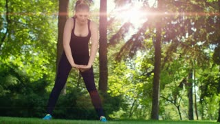 Fitness woman stretching outdoor at sunrise. Sporty woman doing fitness exercises in park at morning. Slim sport woman in sporty clothes doing tilts. Attractive girl workout and fitness outdoor