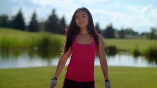 Fitness woman touching hair at park in slow motion. Portrait of asian girl on meadow near lake at summer. Sport girl having rest after workout. Sport woman touching hairs outdoor