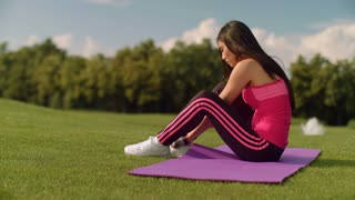 Fitness woman tying shoelaces on yoga mat in summer park. Fitness woman preparing for fitness training. Asian girl tying laces on her running shoes. Sporty woman tying shoe laces on shoes