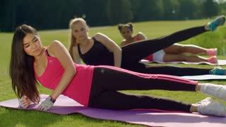 Fitness women doing legs exercise at sunny day. Sport class raises leg in park. Outdoor fitness group. Young girls doing leg lifts on meadow. Aerobics class workout at summer. Fitness training outdoor
