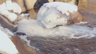 Flowing water. Closeup. Stone covered with snow. Close up. Melting ice. Icy rocks in winter river. Winter cold river. Water motion. River rapids. Fast flowing river. Winter river. River flows.