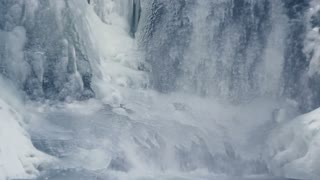 Flowing water in winter. Ice waterfall. Closeup. Winter background. Frozen waterfall. Close up. Falling water. Water fall. Fresh cold water. Arctic environment. Falling water in winter. Ice background