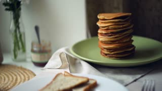 Fried eggs with bread toasts and pancake stack. Panning from pancakes to plate with english breakfast. Close up of traditional meals for breakfast. Cooked eggs, roasted bread slices, stack of pancakes