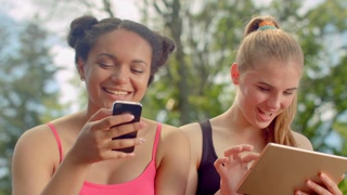 Friends laughing. Multiracial women smiling together. Close up of girlfriends happy faces. Happy friends read good news in internet on tablet. Good news phone. Young women smiling