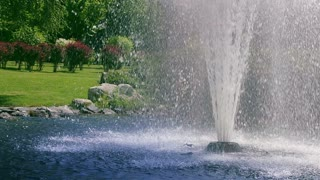 Garden fountain. Fountain splash in slow motion. Water fountain in summer park. Landscape design. Beautiful fountain in national park on background of green field, green trees and bushes of flowers