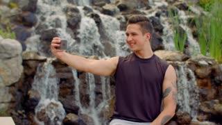 Gay taking selfie near waterfall. Man posing for selfie photo outdoor. Teenager taking photo with phone. Selfie man. Handsome man taking selfie in park. Gay making self portrait. Young man smiling