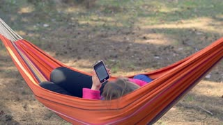 Girl in hammock using smartphone. Young woman surfing internet on mobile phone. People using modern technology. Outdoors recreation. Closeup of girl with phone in hammock