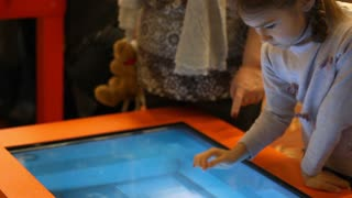 Girl playing video game on big touch screen computer. Girl kid playing touch screen game. Girl touching screen game. Interactive game. Female child playing with interactive screen