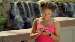 Girl watching photos on smart phone. Latin girl using phone at park. African girl looking at phone screen. Girl phone. Girl using smartphone. Digital life. Modern lifestyle. Girl using mobile phone