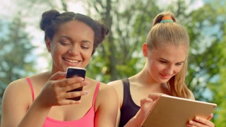 Young women smiling together. Girlfriends smiling together when chatting in social networks. Close up of girls happy faces. Happy people read good news on digital devices. Young women smiling