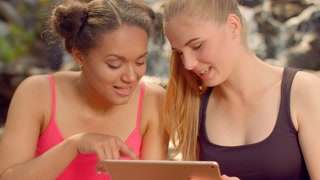 Girls searching internet on tablet outdoor. Close up of women friends talking and surfing internet. Multicultural women using ipad. Two beautiful girls read tablet and talking together