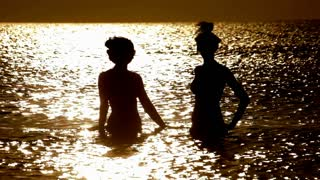 Girls silhouettes dancing in sea at sunset. Happy woman on vacations. People sillhouette in water on sunrise. Sunlight reflection in water. Two young women in ocean on sunset. Sea sunset beauty. Girls fun