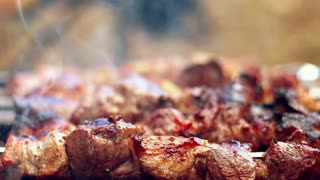 Grilling barbecue meat on wood coal. Man turns skewers. Man cooks appetizing hot shish kebab on metal skewers. Tasty meat pieces with crust. Grilling food. Cooking shashlik on barbecue grill. Closeup