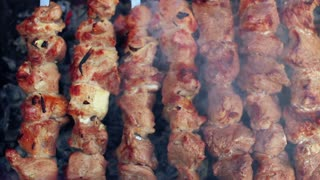 Grilling food on mangal. Man turn skewers with roasted meat. Tasty shish kebab on metal skewers. Closeup. Grilled barbecue meat. Prepared food. Meat with ruddy crust. Macro. Cooking shashlik. Top view