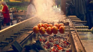 Grilling tomato and meat on skewers. Outdoor grill restaurant. Automatically rotating skewers. Barbecue grill on street food festival. Meat rotating on skewers. Cooking food on barbecue grill
