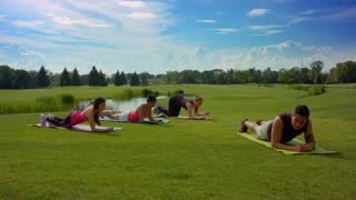 Group of people doing plank exercise on green grass at sunny day. Outdoor fitness class in park. Women group fitness outdoor with fitness trainer. Group fitness people exercising in spring park