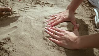 Hands forming heart. Couple hands forming heart shape on sand. People having fun with sand on beach. Beach holiday. Summer vacation. People hands in sand. Love couple hands. Hands heart sand