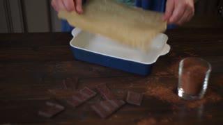 Hands put cooking paper in ceramic form. Baking utensils. Preparing chocolate cake. Man preparing utensils on kitchen table. Cooking utensil. Baking dessert. Cooking cake. Baking cake